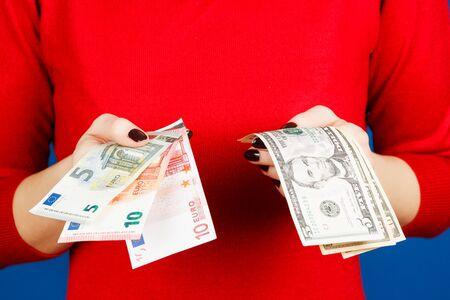dolar: euro y dolar en las manos de una ni�a en un su�ter de color rojo sobre un fondo azul