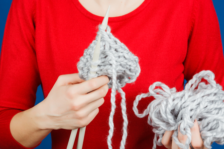 acrylic yarn: Knitting of woolen yarn. Needlework in the hands of women isolated on a blue background