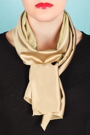 silk scarf: Silk scarf. Beige silk scarf around her neck isolated on blue background. Female accessory.