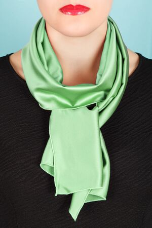 silk scarf: Silk scarf. Green silk scarf around her neck isolated on blue background. Female accessory. Stock Photo