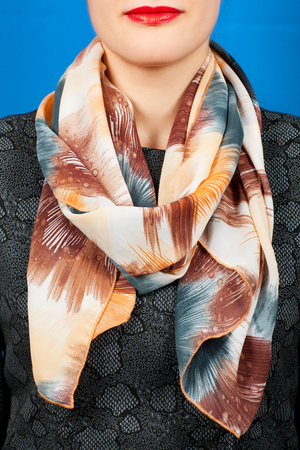 Silk scarf. Beige silk scarf around her neck isolated on blue background. Female accessory.