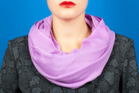 Silk scarf. Lilac silk scarf around her neck isolated on blue background. Female accessory.
