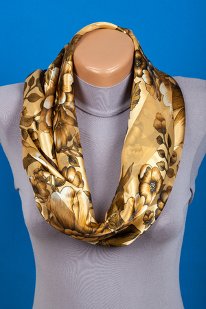 Beige scarf on mannequin isolated on blue background. Female accessory. Фото со стока