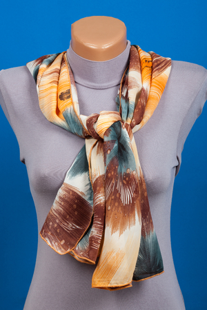 Beige scarf on mannequin isolated on blue background. Female accessory. Фото со стока - 86193231