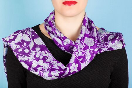 cold: Silk scarf. Lilac silk scarf around her neck isolated on blue background. Female accessory.