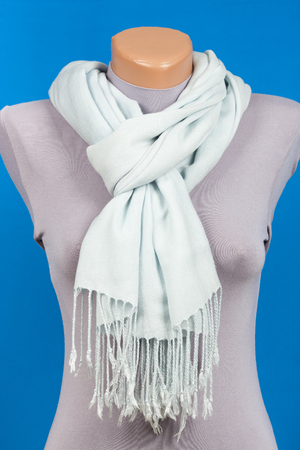 Blue scarf on mannequin isolated on blue background. Female accessory.