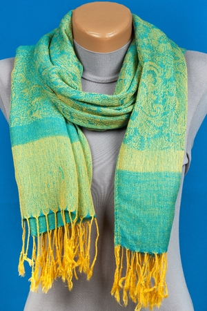 Green scarf on mannequin isolated on blue background. Female accessory.
