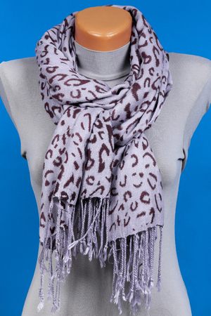 Gray scarf on mannequin isolated on blue background. Female accessory.