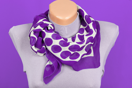 Lilac scarf on mannequin isolated on lilac background. Female accessory.