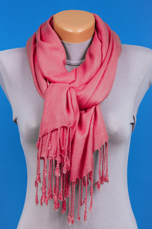 Red scarf on mannequin isolated on blue background. Female accessory. Фото со стока