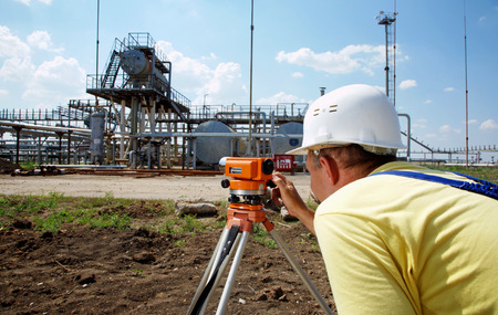 geodesy: Industry worker working with theodolite outdoors Stock Photo