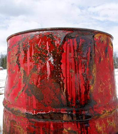 grease paint: Close up oil in red barrel on the background of blue sky