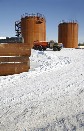 crude: Tank storage crude Oil and fuel truck in winter landscape