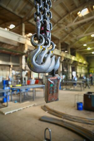 metalline: The steel hooks hanging on the background of industrial premises Stock Photo