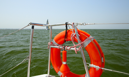 Lifebuoy on a yacht side. Concept of safe sea walk. In the background the yacht under sail Stock Photo