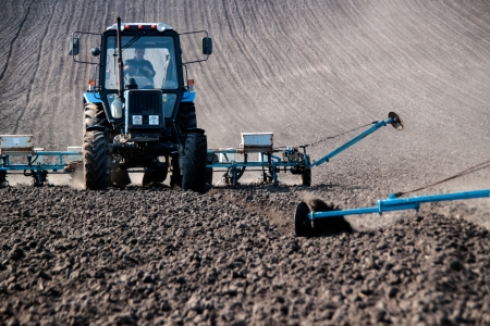 agronomic: Blue tractor with sower on the field in bright sunny spring morning Editorial