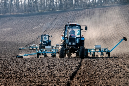 équipement: Tracteurs bleus avec des semeurs sur le terrain en clair matin de printemps ensoleillé Banque d'images