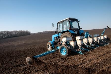 Blauwe tractor met zaaier op het veld in een heldere zonnige lentemorgen Stockfoto