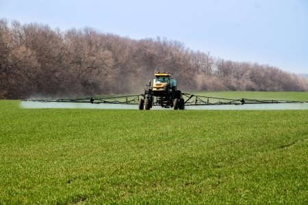 Agricultural machinery spraying the crops with pesticides in springtime photo