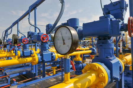 recursos naturales: Pressure meter and red faucet with steel yellow pipe in natural gas treatment plant in bright sunny summer day