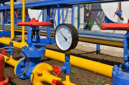 recursos naturales: Contador de la presión y el grifo de acero de color rojo con el tubo amarillo en la planta de tratamiento de gas natural en día soleado de verano