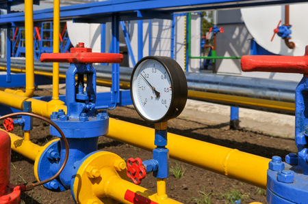 mètre de pression et le robinet rouge avec tubes en acier jaune dans l'usine de traitement de gaz naturel en journée d'été ensoleillée Banque d'images