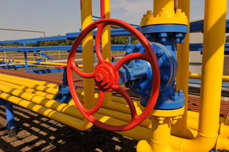 Red faucet with steel pipe in natural gas treatment plant in bright sunny summer day