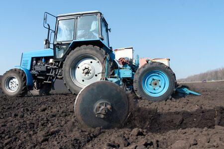 agronomic: Blue tractor with sower on the field in bright sunny spring morning Stock Photo