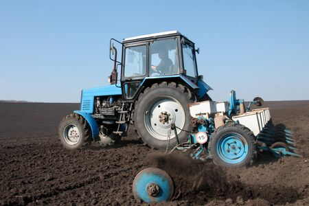 Blue tractor with sower on the field in bright sunny spring morning Stock Photo