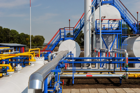 fuel tanks: White fuel tanks and color gas pipes in natural gas treatment plant in bright sunny summer day
