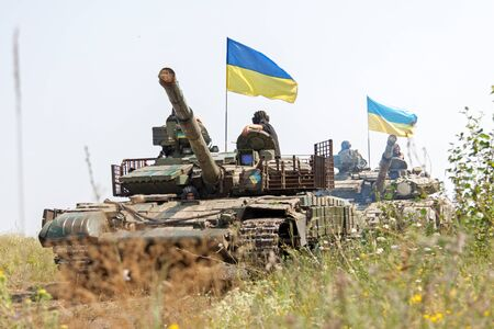 armoring: Main battle tanks under the Ukrainian flags at a firing range in summer day