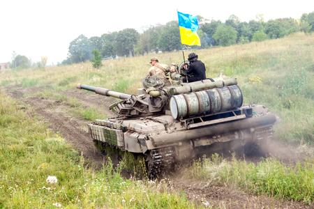 armoring: Main battle tank under the Ukrainian flag at a firing range in summer day