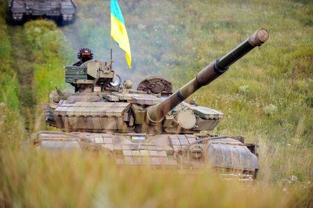 Main battle tank under the Ukrainian flag at a firing range in summer day