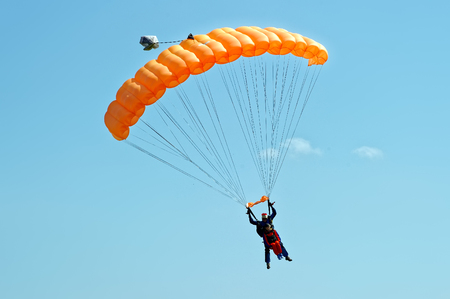 Kharkiv, Ukraine - August 20, 2016: Skydiver flying on orange parachute at the airfield Korotych, Kharkov region, Ukraine on August 20, 2016 Editorial