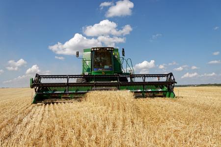 Region Charkiw, Ukraine - 13. Juli 2018: Kombinieren Sie Ernteweizen auf einem Feld im sonnigen Sommertag in der Region Charkiw, Ukraine am 13. Juli 2018.