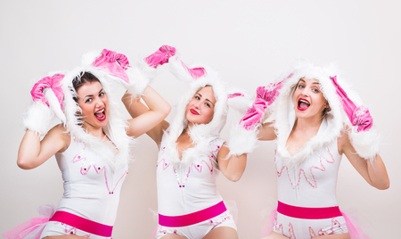 lapin sexy: Image of group of beautiful girls in rabbit costume which feel excited raising their ears up on light gray background