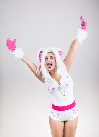 lapin sexy: Picture of happy girl in rabbit costume that feel excited raising her hands up on light gray background