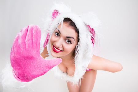 lapin sexy: Portrait of handsome girl in rabbit costume that feel happy say hi putting her hand forward on light gray background Banque d'images