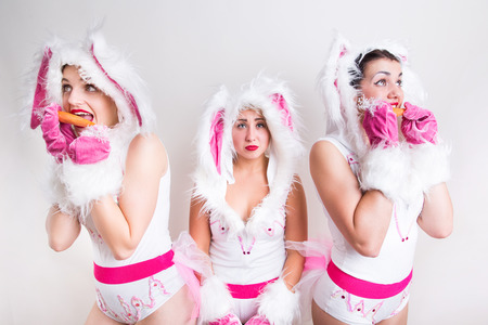 Image of three girls in rabbit costume which eat carrot on light gray background and third bored without carrot Banque d'images