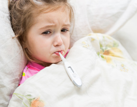 Sick little girl holding thermometer laying in bed with grumpy face