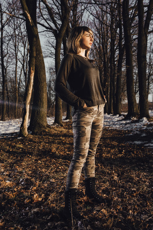 Military style girl in winter forest on background