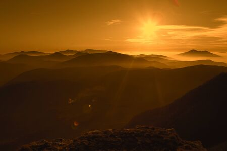 faintly visible: Great sunset on mountains with fog. Beautiful background