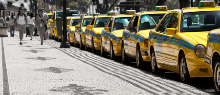 awaiting: FUNCHAL, MADEIRA - JUNE 15, 2011: Taxis line up awaiting customers on the street of Funchal
