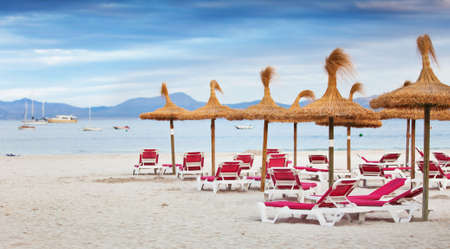 sunbeds: the beach with sunbeds and parasols of straw