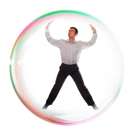 Joven hombre de negocios dentro de una burbuja de jabón, aisladas sobre fondo blanco. Foto de archivo