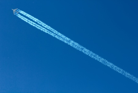 Diagonal airplane trace against blue sky.  photo