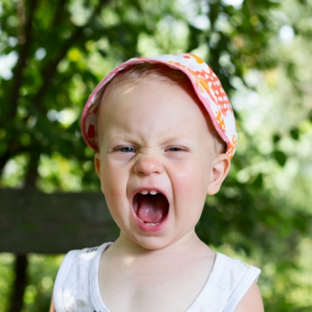 unhappy family: Baby boy (1 year) screaming on nature background. Stock Photo