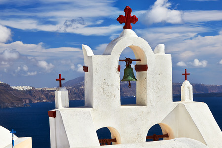 Bell tower of church against the  Santorini island, Greece. photo