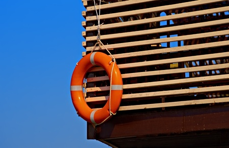 Lifebuoy on a wooden plank wall against blue sky Stock Photo