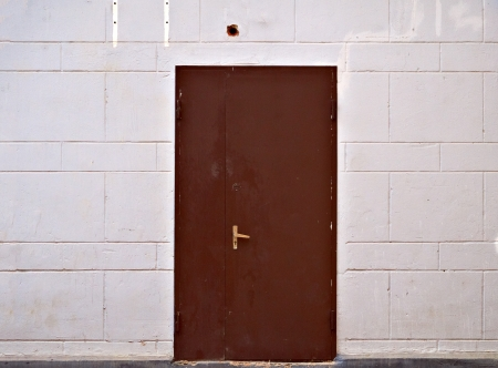 Rusty metal door in beige block wall                                Stock Photo - 15768730